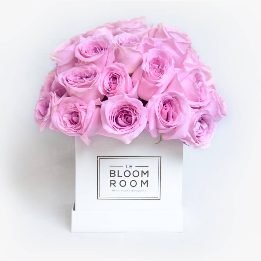 Arreglo floral de rosas moradas en caja