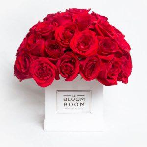 Caja blanca con rosas rojas en esfera